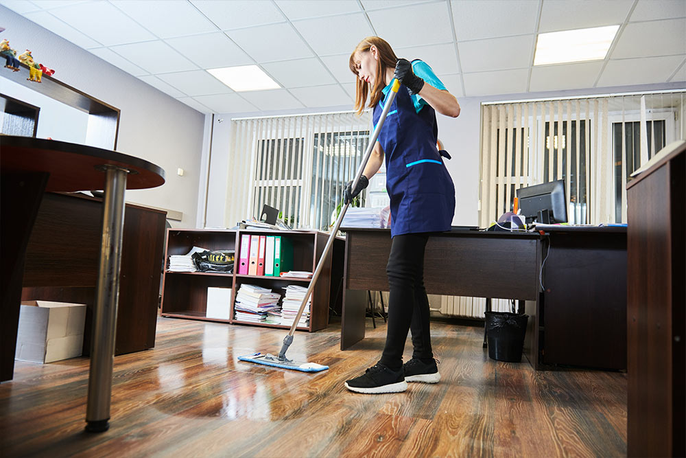 A lady cleaning brown hardwood floor with a mop in an office.