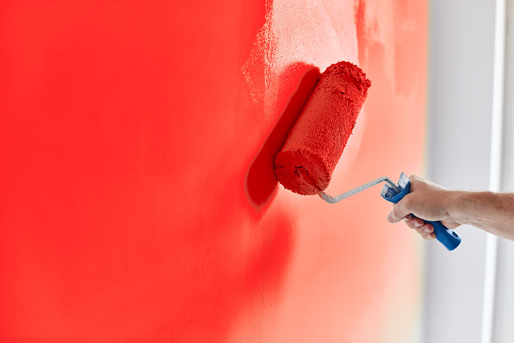 A painter painting a wall red.